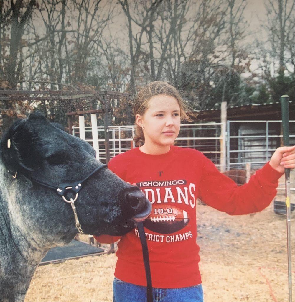 Teenage girl leading a blue roan steer