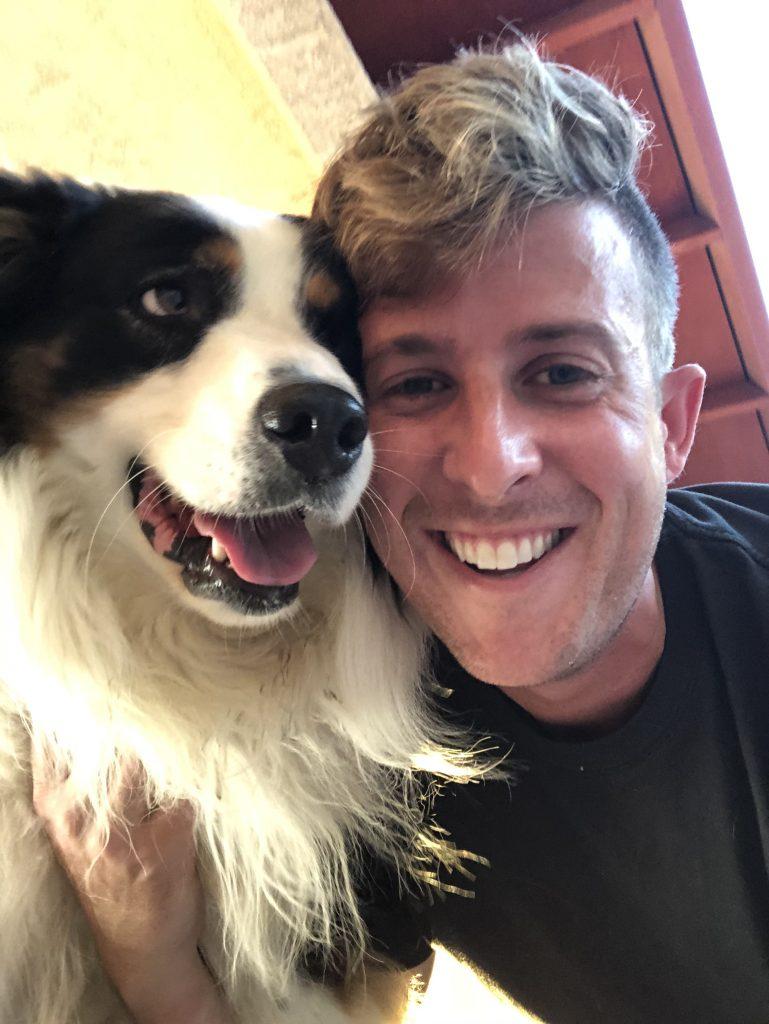 Man snuggling with Australian Shepard dog.